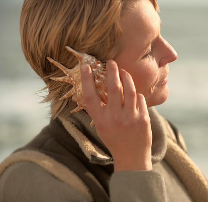 Eine Frau hält sich eine große Muschel ans Ohr und horcht hinein